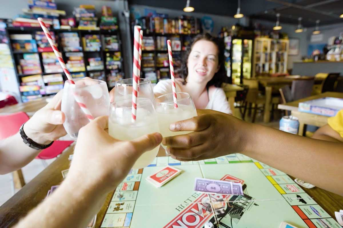 Four friends clink glasses of lemonade while playing Monopoly in a board games café