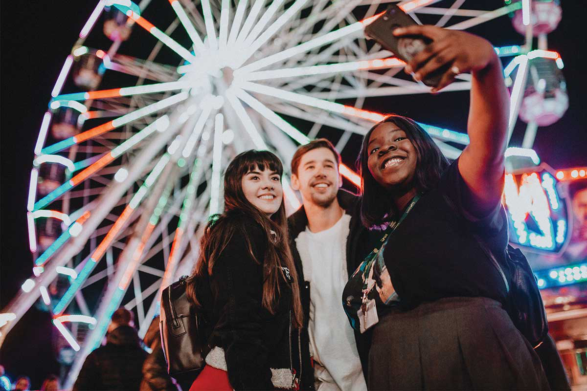 A group of three friends stop for a selfie in front of the big wheel at 船体公平 不能 £26.54 £41.46 £44.54 £27.67 £26.13 £1.12.