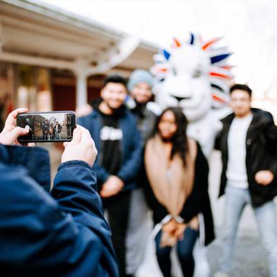 Four friends pose with Pride the Lion, Team GB's mascot, for a photo outside 船壳 University Union.